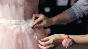 Ο σχεδιαστής μόδας ράβει ένα γαμήλιο φόρεμα από στενό επάνω δαντελλών φιλμ μικρού μήκους