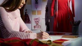 Ο σχεδιαστής σύρει ένα σκίτσο στο υπόβαθρο είναι μανεκέν με ένα κόκκινο φόρεμα κλείστε επάνω απόθεμα βίντεο