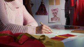 Ο σχεδιαστής χεριών επισύρει την προσοχή ένα σκίτσο ενός φορέματος, σε έναν πίνακα υφασμάτων, για την προσαρμογή κλείστε επάνω φιλμ μικρού μήκους