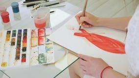 Ο σχεδιαστής χρωματίζει ένα σκίτσο του μελλοντικού φορέματός της φιλμ μικρού μήκους