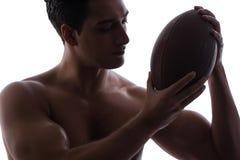 Ο σχισμένος νεαρός άνδρας με το αμερικανικό ποδόσφαιρο που απομονώνεται στο λευκό στοκ φωτογραφίες με δικαίωμα ελεύθερης χρήσης