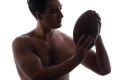 Ο σχισμένος νεαρός άνδρας με το αμερικανικό ποδόσφαιρο που απομονώνεται στο λευκό στοκ φωτογραφία