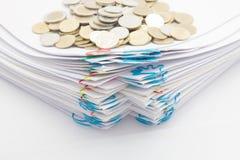 Ο σωρός της γραφικής εργασίας με το ζωηρόχρωμο paperclip έχει τα χρυσά νομίσματα σωρών Στοκ Εικόνες