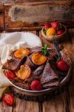 Ο σωρός της σοκολάτας crepes διακοσμημένος με τη φράουλα και τα ψημένα στη σχάρα βερίκοκα στο ξύλινο υπόβαθρο Εκλεκτική εστίαση Στοκ Εικόνα