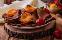 Ο σωρός της σοκολάτας crepes διακοσμημένος με τη φράουλα και τα ψημένα στη σχάρα βερίκοκα στο ξύλινο υπόβαθρο Εκλεκτική εστίαση Στοκ εικόνα με δικαίωμα ελεύθερης χρήσης