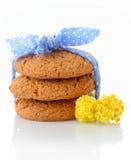 Ο σωρός τριών σπιτικών oatmeal μπισκότων έδεσε με την μπλε κορδέλλα στα μικρά άσπρα σημεία Πόλκα και τα μικροσκοπικά κίτρινα λουλ Στοκ Εικόνες