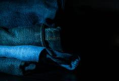 Ο σωρός των διπλωμένων ενδυμάτων, τζιν παντελόνι ασθμαίνει, σκούρο μπλε παντελόνι τζιν στο σκοτεινό υπόβαθρο Στοκ Εικόνα