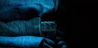 Ο σωρός των διπλωμένων ενδυμάτων, τζιν παντελόνι ασθμαίνει, σκούρο μπλε παντελόνι τζιν στο σκοτεινό υπόβαθρο Στοκ Εικόνες