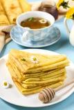 Ο σωρός των λεπτών τηγανιτών crepes για το πρόγευμα με το μέλι και το τσάι Στοκ εικόνες με δικαίωμα ελεύθερης χρήσης