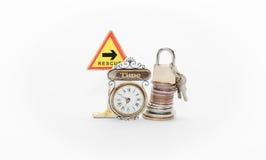 ο σωρός των νομισμάτων χρημάτων με την κλειδαριά και τα κλειδιά μαξιλαριών, τα ρολόγια, το οδικό σημάδι με το βέλος και η λέξη δι Στοκ Εικόνες
