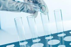Ο σωλήνας δοκιμής εκμετάλλευσης χεριών χύνει τις χημικές ουσίες Στοκ φωτογραφία με δικαίωμα ελεύθερης χρήσης