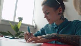 Ο σύγχρονος έξυπνος κορίτσι-σχεδιαστής κάνει τα σκίτσα σε ένα φωτεινό εσωτερικό φιλμ μικρού μήκους