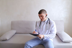 Ο σύγχρονος αρσενικός γιατρός μιλά στον ασθενή από το bluetooth και γράφει στο ρ Στοκ Εικόνες