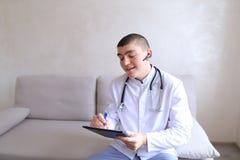 Ο σύγχρονος αρσενικός γιατρός μιλά στον ασθενή από το bluetooth και γράφει στο ρ Στοκ φωτογραφία με δικαίωμα ελεύθερης χρήσης