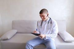 Ο σύγχρονος αρσενικός γιατρός μιλά στον ασθενή από το bluetooth και γράφει στο ρ Στοκ εικόνα με δικαίωμα ελεύθερης χρήσης