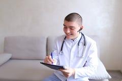 Ο σύγχρονος αρσενικός γιατρός μιλά στον ασθενή από το bluetooth και γράφει στο ρ Στοκ Εικόνα