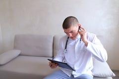 Ο σύγχρονος αρσενικός γιατρός μιλά στον ασθενή από το bluetooth και γράφει στο ρ Στοκ Φωτογραφίες