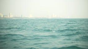 Ο σύγχρονος αστικός ορίζοντας Ανάχωμα τοπίων πόλεων με τους πολύ υψηλούς ουρανοξύστες άποψη από τη θάλασσα, 4k, θαμπάδα φιλμ μικρού μήκους
