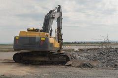 Ο σύγχρονος εκσκαφέας εκτελεί την εργασία ανασκαφής για το εργοτάξιο οικοδομής στοκ φωτογραφία
