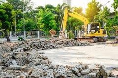 Ο σύγχρονος εκσκαφέας εκτελεί την εργασία ανασκαφής για το εργοτάξιο οικοδομής στοκ εικόνα