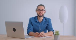 Ο σύγχρονος επιχειρηματίας με το ponytail και eyeglasses χαμογελά στο παιχνίδι καμερών με το μολύβι στο άσπρο γραφείο φιλμ μικρού μήκους