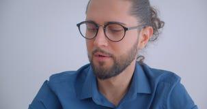 Ο σύγχρονος επιχειρηματίας με το ponytail και eyeglasses χαμογελά συγκρατημένα στη κάμερα που απομονώνεται στο άσπρο υπόβαθρο φιλμ μικρού μήκους