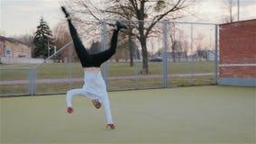 Ο σύγχρονος νέος καυκάσιος τύπος εκτελεί τα ακροβατικά τεχνάσματα, σύνθετα στοιχεία στην οδό στην παιδική χαρά απόθεμα βίντεο