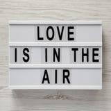 """Ο σύγχρονος πίνακας με το κείμενο """"αγάπη είναι στον αέρα """"σε μια άσπρη ξύλινη επιφάνεια Βαλεντίνος ` s ημέρα στις 14 Φεβρουαρίου στοκ φωτογραφία με δικαίωμα ελεύθερης χρήσης"""