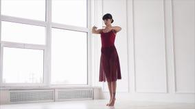Ο σύγχρονος χορευτής εκτελεί τις κλασικές θέσεις μπαλέτου, που στέκονται σε μια άσπρη αίθουσα απόθεμα βίντεο