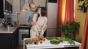 Ο σύζυγος αγκαλιάζει τη σύζυγό του στην κουζίνα και τη βοήθεια της μπριζόλας της τα λαχανικά για τη σαλάτα απόθεμα βίντεο