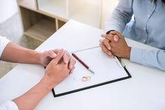 Ο σύζυγος και η σύζυγος διαβάζουν τη συμφωνία διαζυγίου και υπογράφουν το διάταγμα της διάλυσης διαζυγίου ή της ακύρωσης της αρχε στοκ εικόνες με δικαίωμα ελεύθερης χρήσης