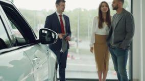 Ο σύζυγος και η σύζυγος επιλέγουν το πρώτο αυτοκίνητό τους μαζί και μιλούν στο βέβαιο πωλητή στη έκθεση αυτοκινήτου, ευτυχής γυνα απόθεμα βίντεο