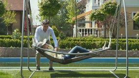 Ο σύζυγος ταλαντεύεται τη σύζυγό του στο καπέλο στην αιώρα στον κήπο απόθεμα βίντεο