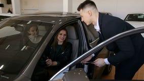 Ο σύμβουλος πωλήσεων παρουσιάζει τα νέα κορίτσια ένα νέο αυτοκίνητο για να αγοράσει απόθεμα βίντεο