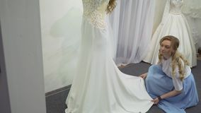 Ο σύμβουλος βοηθά τη μελλοντική νύφη για να επιλέξει το γαμήλιο φόρεμα φιλμ μικρού μήκους