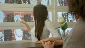 Ο σύμβουλος πωλητών της Νίκαιας προσφέρει να επιλέξει κάποια κοσμήματα σε έναν πελάτη σε ένα κατάστημα κοσμήματος απόθεμα βίντεο