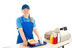 Ο ταμίας εφήβων εξυπηρετεί το γρήγορο φαγητό Στοκ εικόνα με δικαίωμα ελεύθερης χρήσης