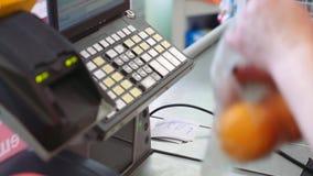 Ο ταμίας ζυγίζει τα πορτοκάλια στον έλεγχο στην υπεραγορά Αγορά των προϊόντων απόθεμα βίντεο