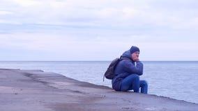 Ο ταξιδιώτης ατόμων κάθεται στην παλαιά προκυμαία εν πλω στη χειμερινή ημέρα και εξετάζει seascape απόθεμα βίντεο