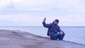 Ο ταξιδιώτης ατόμων κάνει selfie στο smartphone να καθίσει στην παλαιά προκυμαία εν πλω το χειμώνα απόθεμα βίντεο
