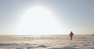 Ο ταξιδιώτης ατόμων περπατά σε μια χιονισμένη περιοχή στα βουνά Μπροστινή άποψη από μακρυά φιλμ μικρού μήκους