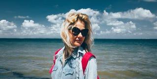 Ο ταξιδιώτης κοριτσιών με ένα σακίδιο πλάτης στέκεται στο υπόβαθρο της θάλασσας και απολαμβάνει το όμορφο τοπίο Έννοια του ταξιδι στοκ εικόνες