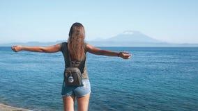 Ο ταξιδιώτης κοριτσιών με το σακίδιο πλάτης διαδίδει τα όπλα της ευρέως, απολαμβάνει τη θέα του ωκεανού, βουνά φιλμ μικρού μήκους