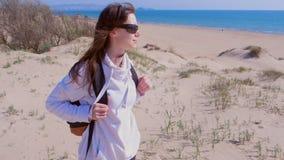 Ο ταξιδιώτης κοριτσιών με το σακίδιο πλάτης κοιτάζει γύρω στην παραλία άμμου θάλασσας στις διακοπές απόθεμα βίντεο