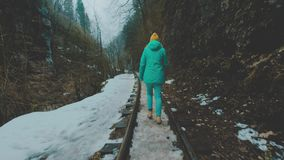Ο ταξιδιώτης κοριτσιών πηγαίνει κατά μήκος του στενού σιδηροδρόμου μετρητών Για να συναντήσει την περιπέτεια Σε ένα θλιβερό φαράγ απόθεμα βίντεο