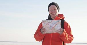 Ο ταξιδιώτης με το χάρτη εξετάζει τη κάμερα και το χαμόγελο απόθεμα βίντεο