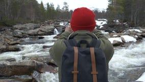 Ο ταξιδιώτης σε ένα κόκκινο καπέλο με ένα σύνολο σακιδίων πλάτης σταμάτησε πίσω για να παίρνει μια φωτογραφία ενός ποταμού βουνών απόθεμα βίντεο