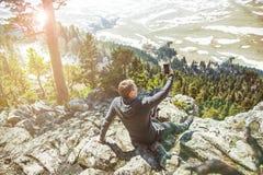 Ο ταξιδιώτης τύπων παίρνει τις εικόνες μόνου σε ένα smartphone στο υπόβαθρο των βουνών Άποψη από την πλάτη του τουρίστα Στοκ εικόνα με δικαίωμα ελεύθερης χρήσης