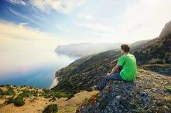 Ο ταξιδιώτης χαλαρώνει στην άκρη βουνών Στοκ Φωτογραφία