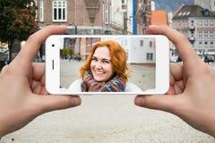 Ο ταξιδιώτης γυναικών επικοινωνεί μέσω ενός smartphone Στοκ εικόνα με δικαίωμα ελεύθερης χρήσης